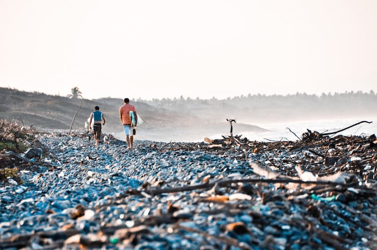 surfers walking on cobblestone beach