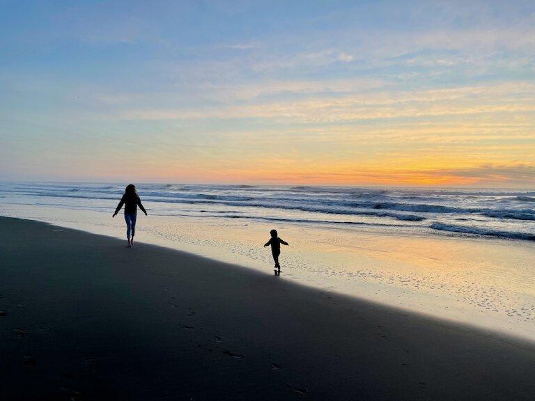 john, sierra, and stella enjoying the sunset at ocean beach
