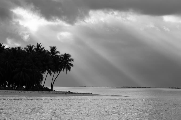 black and white photo of island and clouds